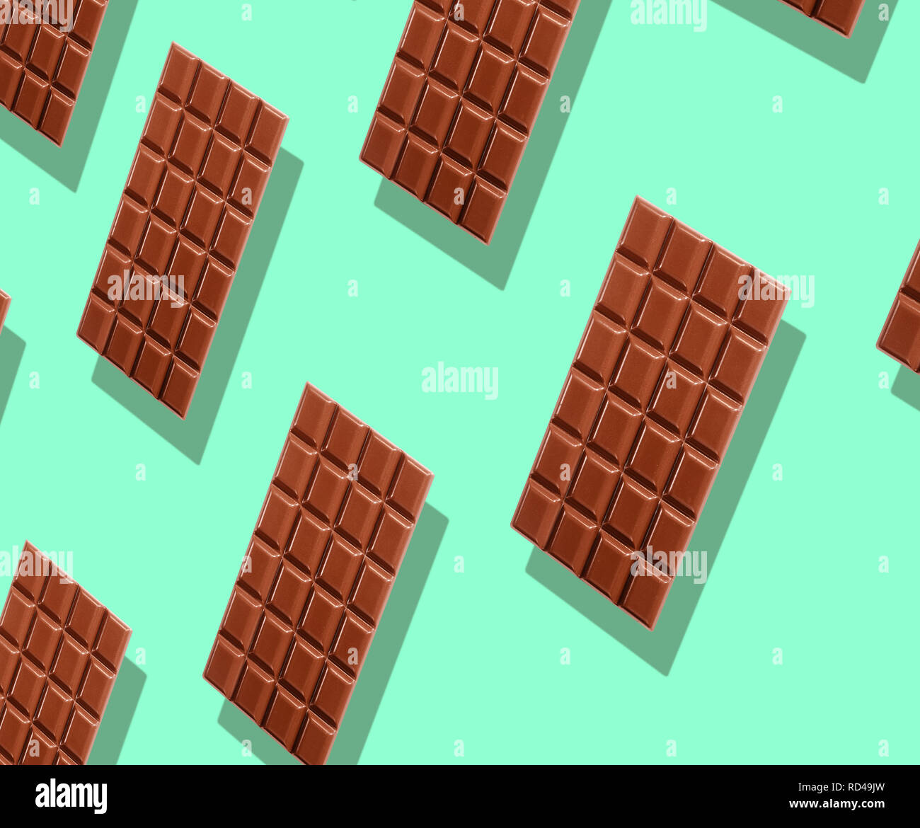 Pattern of whole delicious milk chocolate tablets hovering over green background with shadow in full frame - Stock Image