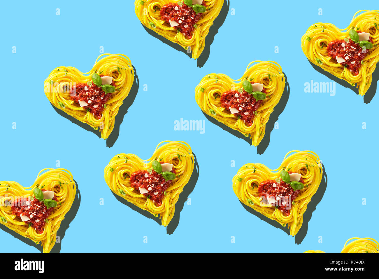 Decorative hearts of pasta of cooked yellow spaghetti with tomatoes, basil and parmesan cheese toping, viewed from above in full frame on light blue b - Stock Image