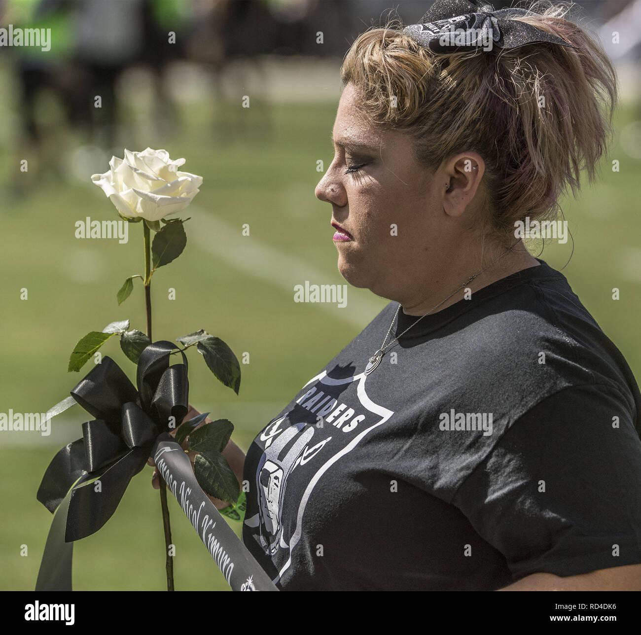 Oakland, California, USA. 8th Oct, 2017. Volunteer holds black ribbon with Las Vegas shooting victim Teresa Nicol Kimura on it during moment of silence on Sunday, October 8, 2017, at Oakland-Alameda County Coliseum in Oakland, California. The Ravens defeated the Raiders 30-17. Credit: Al Golub/ZUMA Wire/Alamy Live News - Stock Image