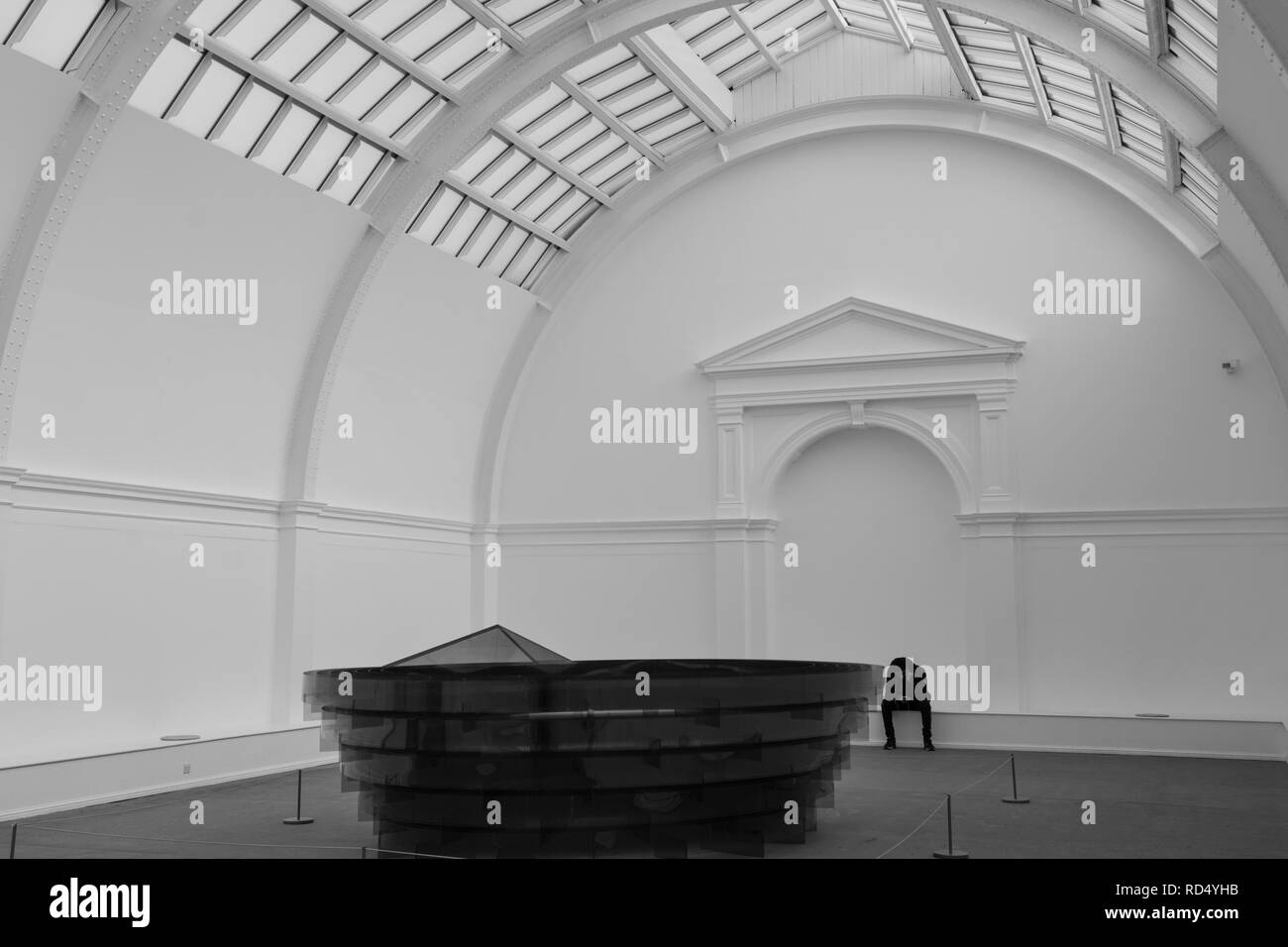 Man sat alone on a ledge in the Central Court at Leeds Art Gallery, West Yorkshire, England, UK. Stock Photo