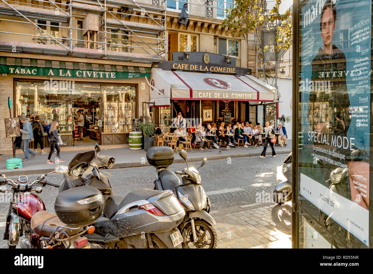 Scooters parked in a Paris street next to an advertising board with people sitting outside having lunch at Cafe De La Comedie, Rue Saint Honoré ,Paris - Stock Image