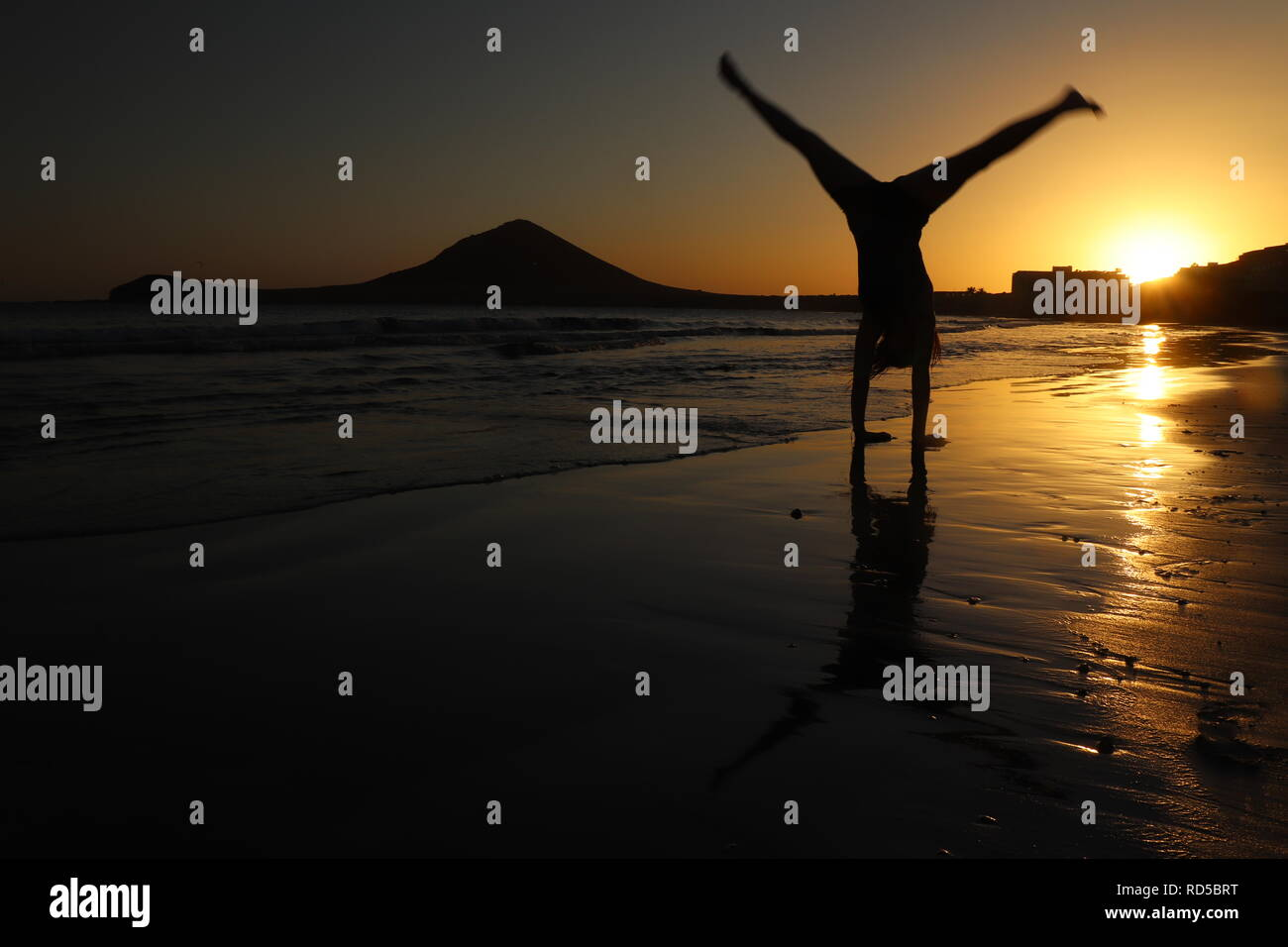 Girl doing a cartwheel on the beach at sunset - Stock Image
