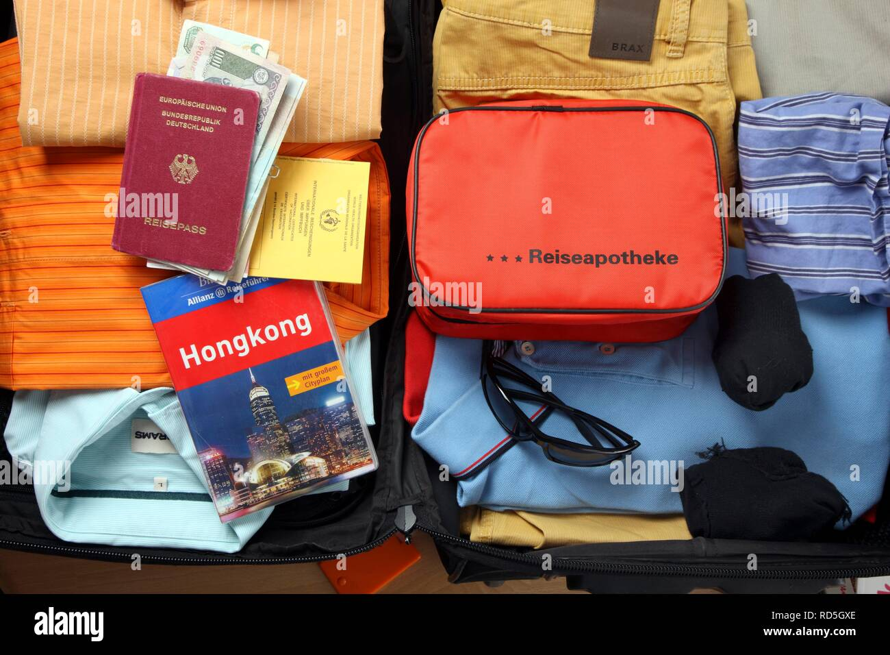 Holiday luggage, first-aid kit, passport, vaccination card, travel guide Stock Photo