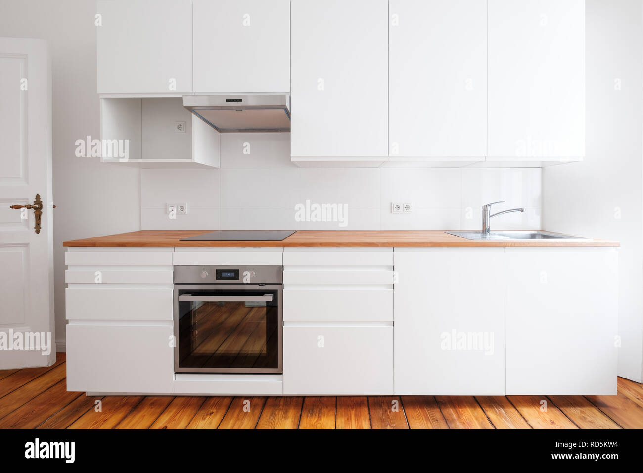 White Kitchenette , Newly Built In Kitchen Furniture Frontal View With  Wooden Worktop And Board Floor