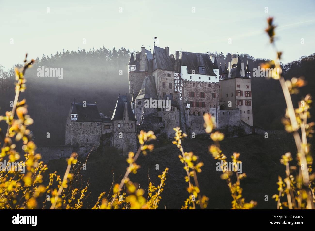 Beautiful view of famous Eltz Castle in scenic golden morning light at sunrise in fall, Wierschem, Rheinland-Pfalz, Germany - Stock Image