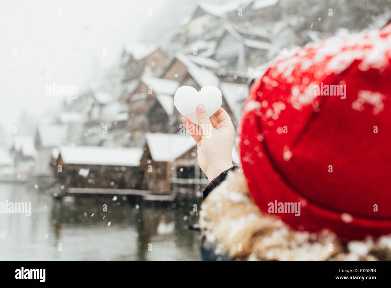 Young blonde woman in a red hat holding snow ball in a shape of a heart in front of the old village of Hallstatt, Austria. Blurry background, shallow  Stock Photo