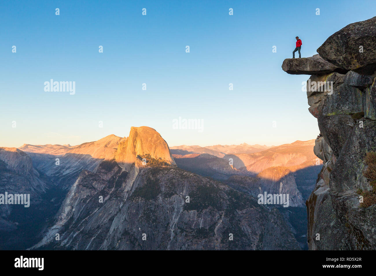 A fearless hiker is standing on an overhanging rock enjoying the view towards famous Half Dome at Glacier Point overlook in beautiful evening twilight Stock Photo