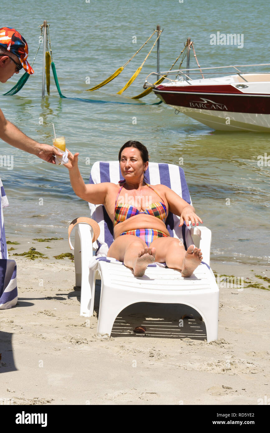 Middle aged woman sunbathing and getting a drink at a beach bar on Coroa do Aviao islet - Stock Image