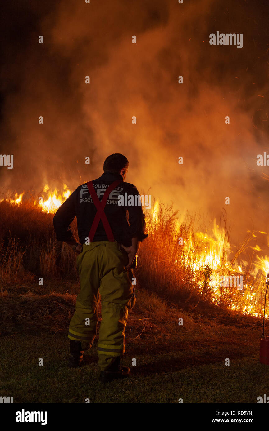 Teralba, NSW/Australia - October 24, 2012: Fireman or firefighter supervising backburning and extinguishing a wildfire grass and bushfire to protect r - Stock Image