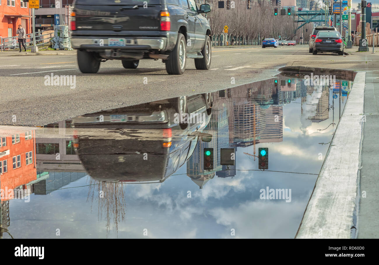 Reflections of a car and city buildings on a large rainwater puddle after a winter storm in downtown Seattle, Washington, United States. Stock Photo