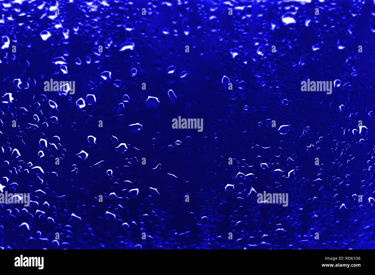High contrast photo of drops of rain on a window glass with vivid navy blue color Stock Photo