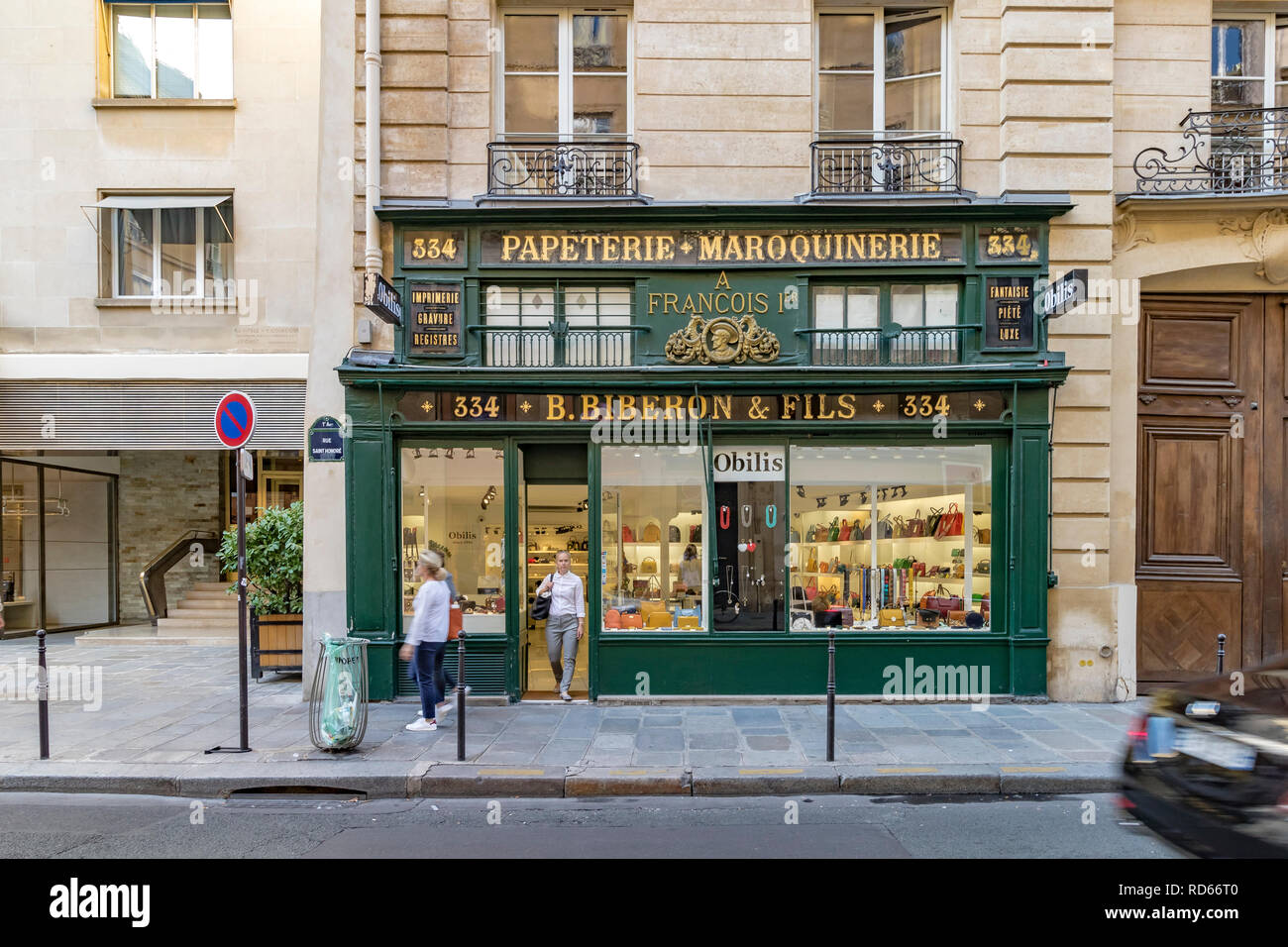 A walking walking out of the door of B. Biberon & Fils  a retailer  of luxury leather goods and stationery, Paris, France - Stock Image