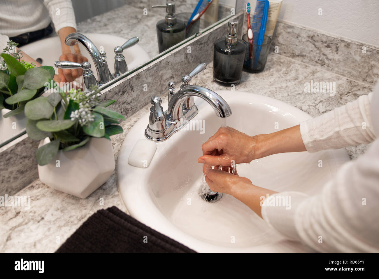 Young Caucasian Female Hands Lathering White Bar Hand Soap for Washing and Personal Hygiene, and Then Rinsing Hand Under Sink Water at Clean Bathroom - Stock Image