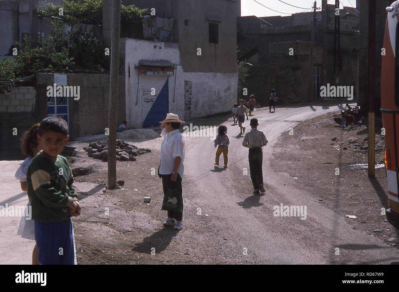 Scene of children playing on a dirt road in the town of Qalaat al-Madiq, Syria, June, 1994. () - Stock Image