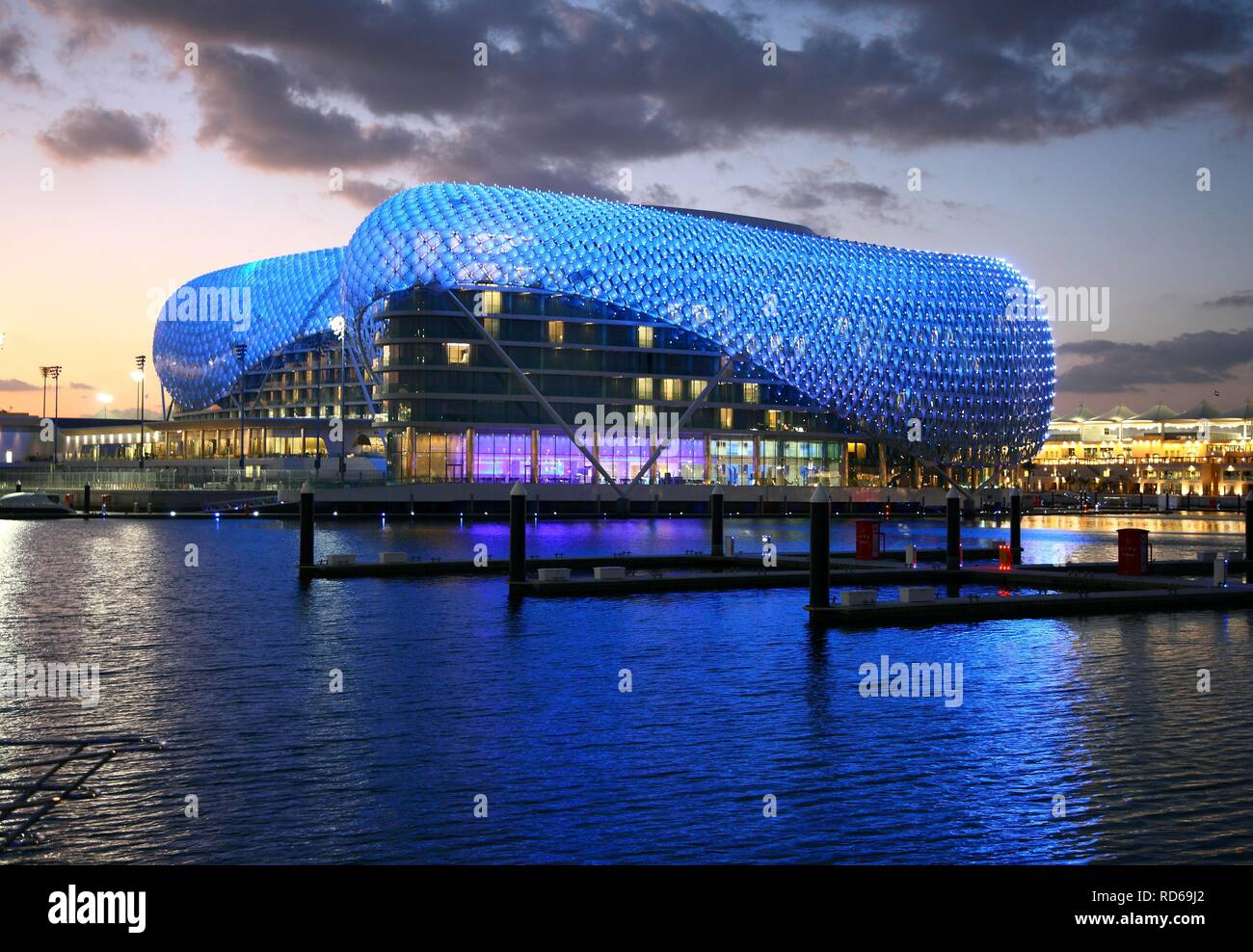 Yas Hotel on Yas Island, futuristic luxury hotel in the middle of the Formula 1 race track of Abu Dhab at dusk - Stock Image