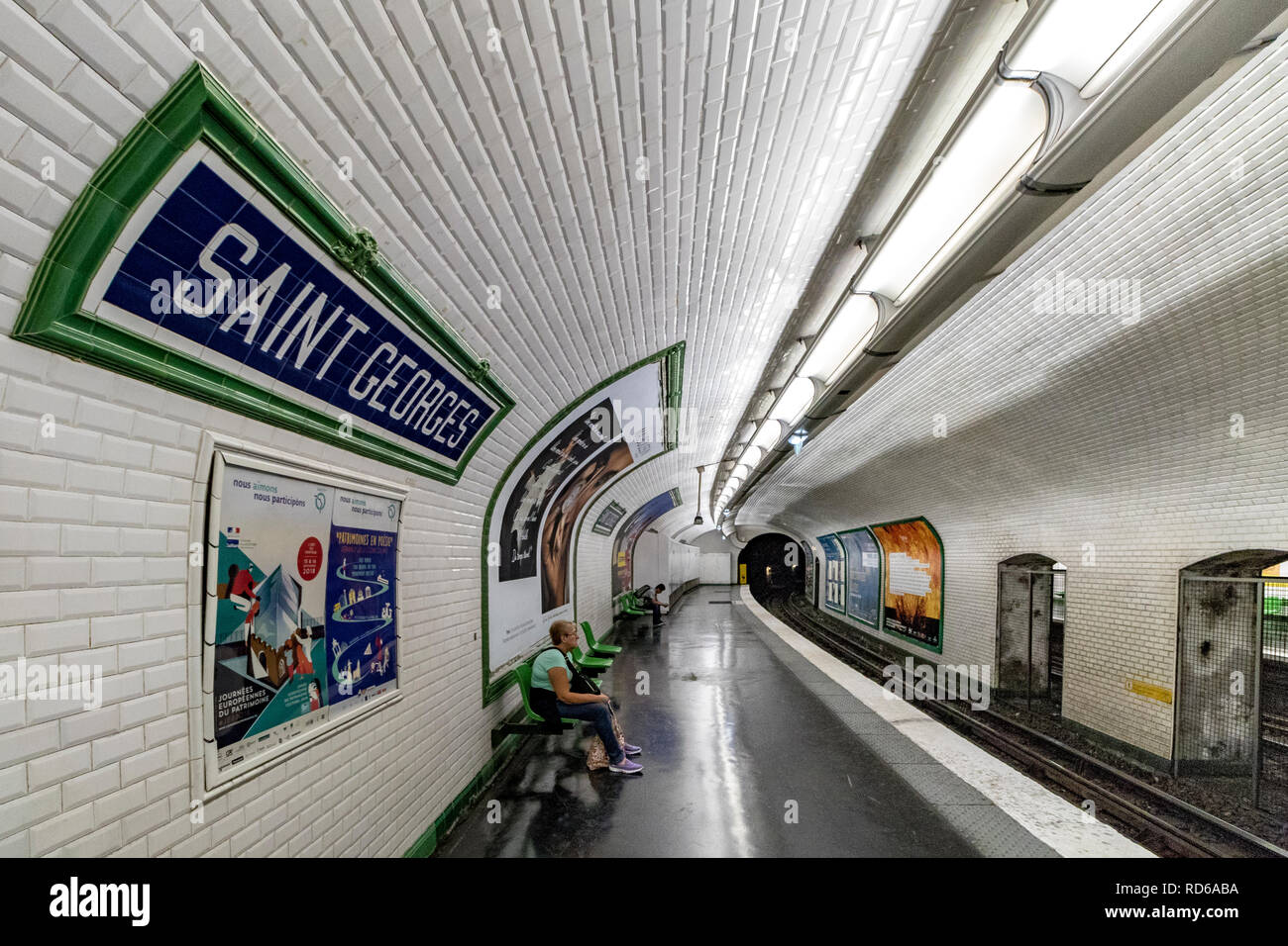People waiting for a Paris Metro train at St Georges metro station , a white ceramic tiled staion in Paris,France - Stock Image