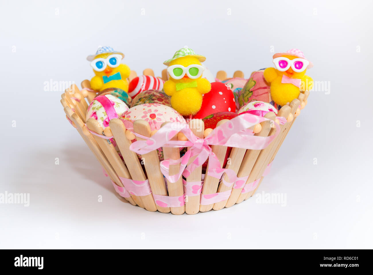 Easter decoration with colorful eggs and funny chicks in wooden basket isolated on white background. Easter holiday concept. Stock Photo