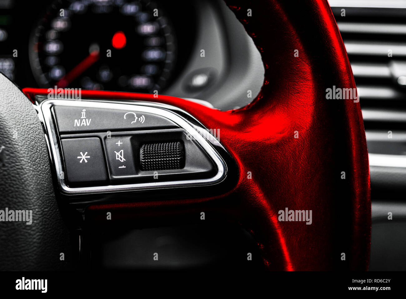 Modern car interior. Red Steering wheel with media phone control buttons, navigation multimedia system background. Car interior details. Car detailing - Stock Image