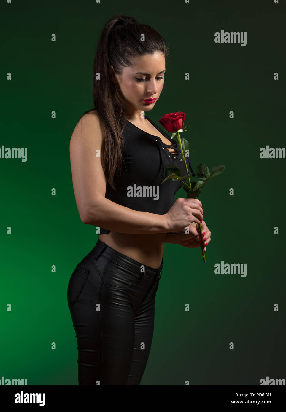 young woman in black outfit holding red rose Stock Photo