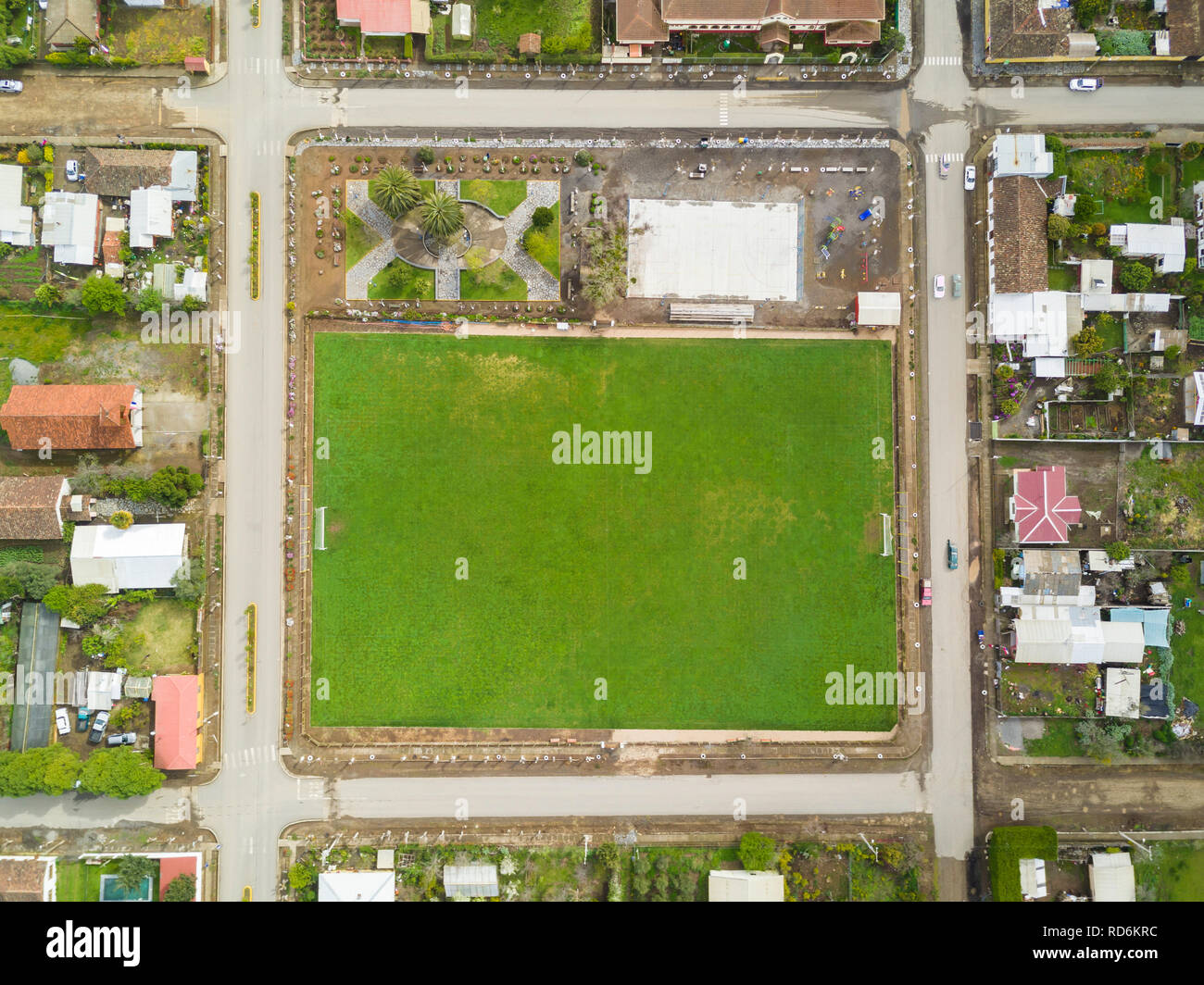 An aerial view of Chile countryside from the drone, a small grass football field as the Main Square inside a new and symmetrical urban planning - Stock Image
