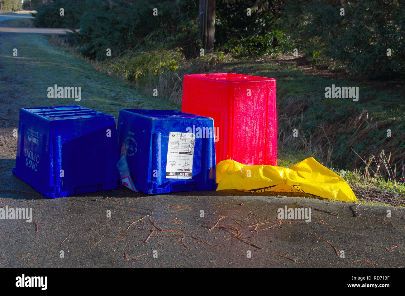 Empty upside down Blue Box recycling bins at curbside with a red bin for plastics and a yellow bag for cardboard. Stock Photo