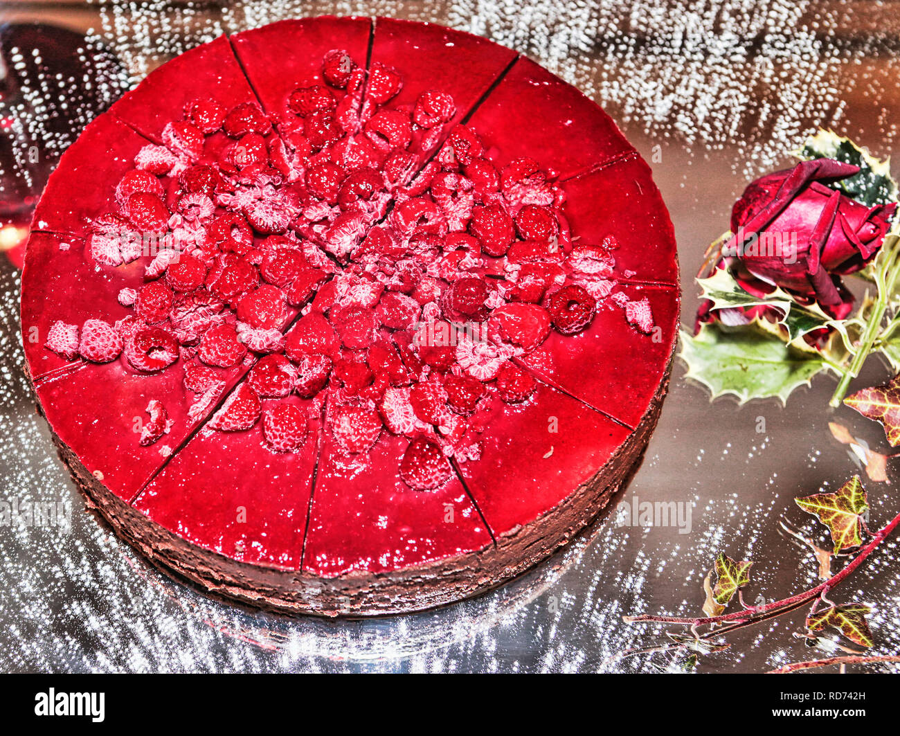 Multi Layer cake filled with cream and raspberries served on a mirror bowl dusted with icing sugar and decorative plants - Stock Image