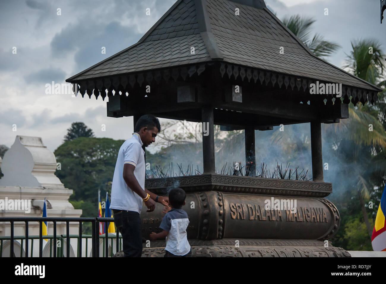 Kandy, Sri Lanka :  Temple of the Tooth (Sri Dalada Maligawa), an Indian man and child light incense to offer up prayers to Buddha - Stock Image