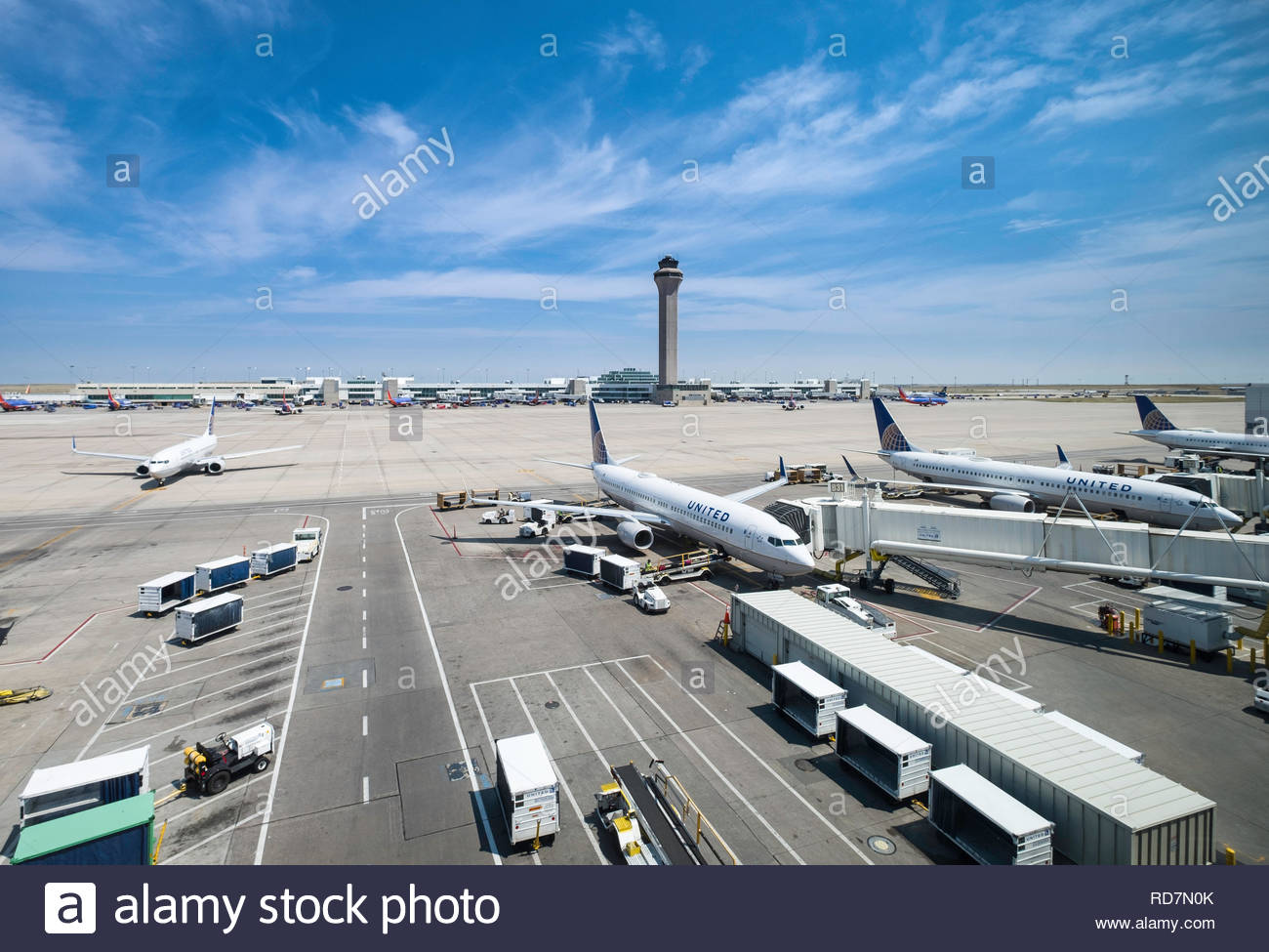 United Airlines commercial passenger jet aircraft parked at concourse B with concourse C and control tower in the background, Denver International Air - Stock Image