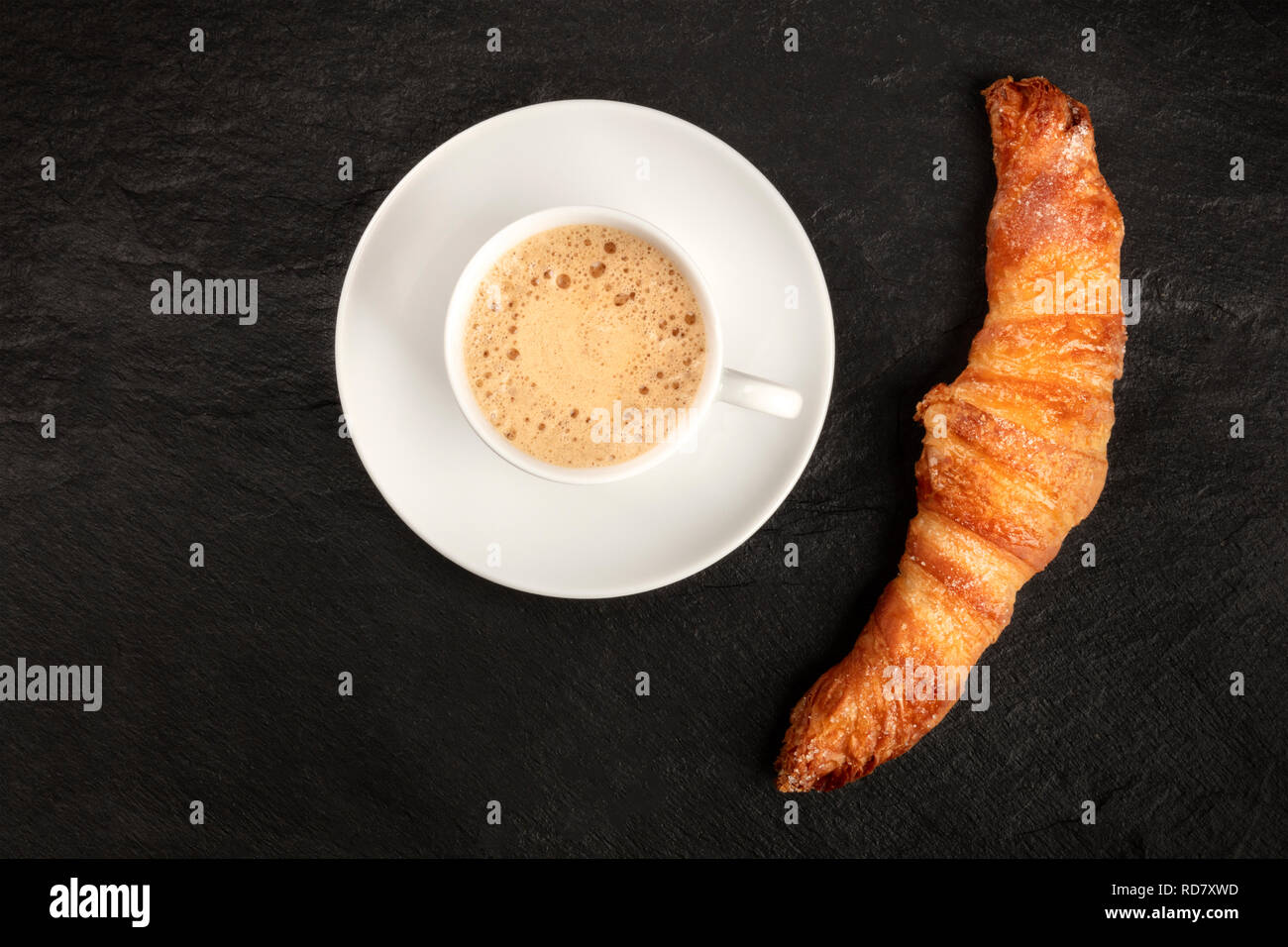 A photo of a croissant with a cup of coffee, shot from above on a black background with copy space - Stock Image