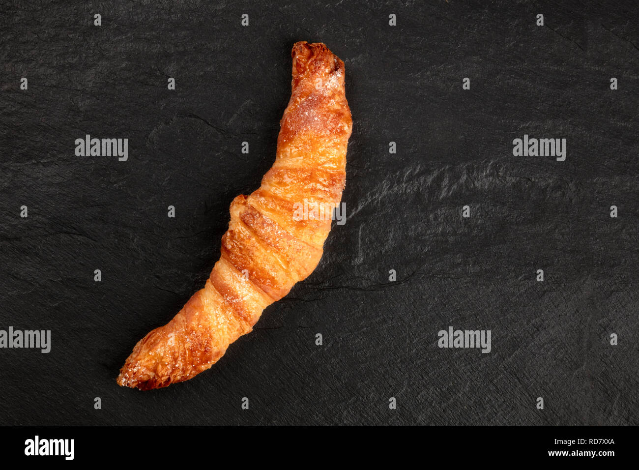 A photo of a croissant on a black background, shot from above with copy space - Stock Image