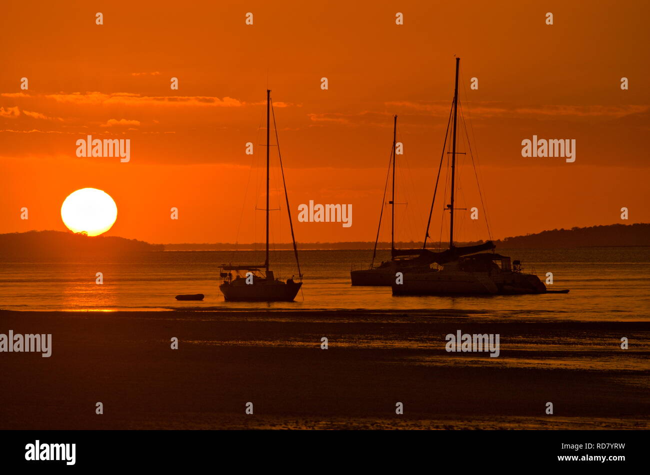 Dramatic red sunset over three yachts docked in harbour on Fraser Island while orange light reflects off ocean and wet sand Stock Photo