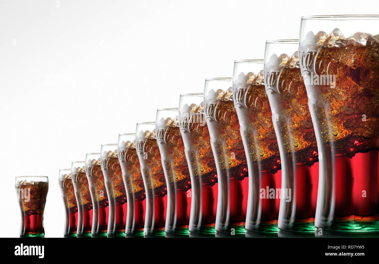 Glasses of Coca Cola with ice, in a row against a white background - Stock Image