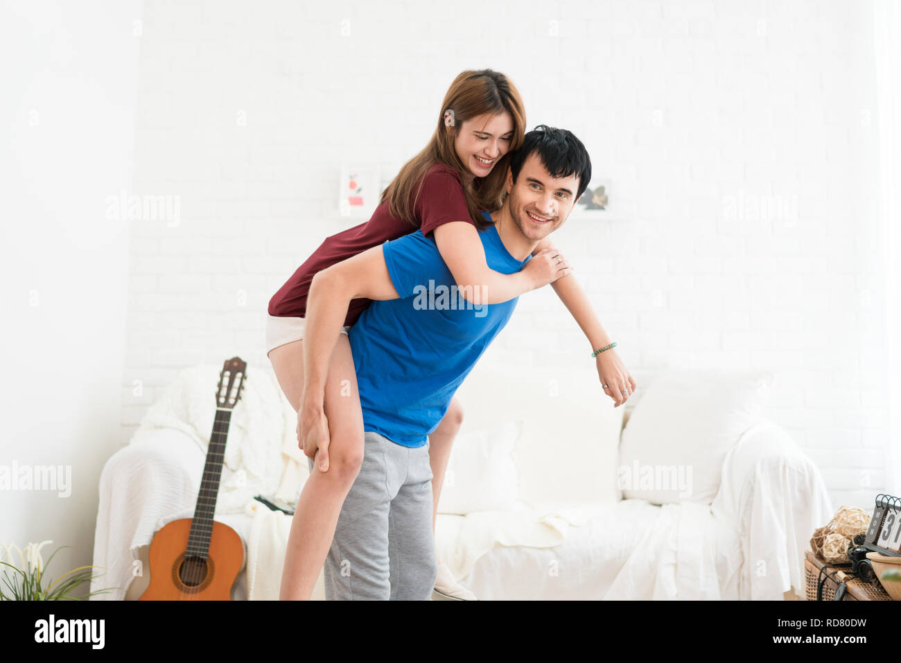 Romantic happy young couple relax at modern home indoors and have fun. Couple hugging and smiling while spending time together. Stock Photo