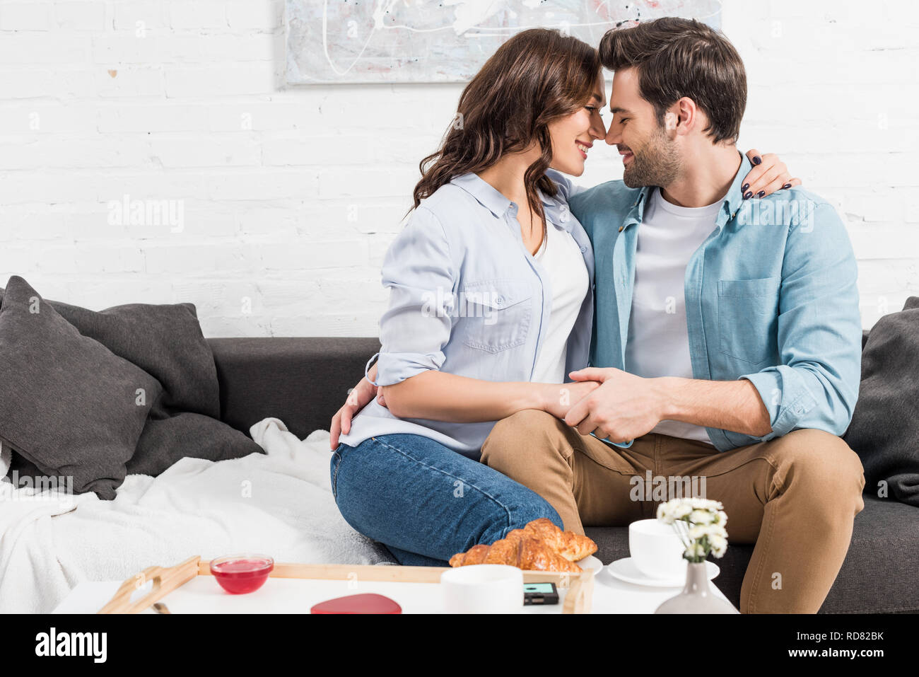 couple sitting on couch and tenderly embracing while having breakfast at home - Stock Image