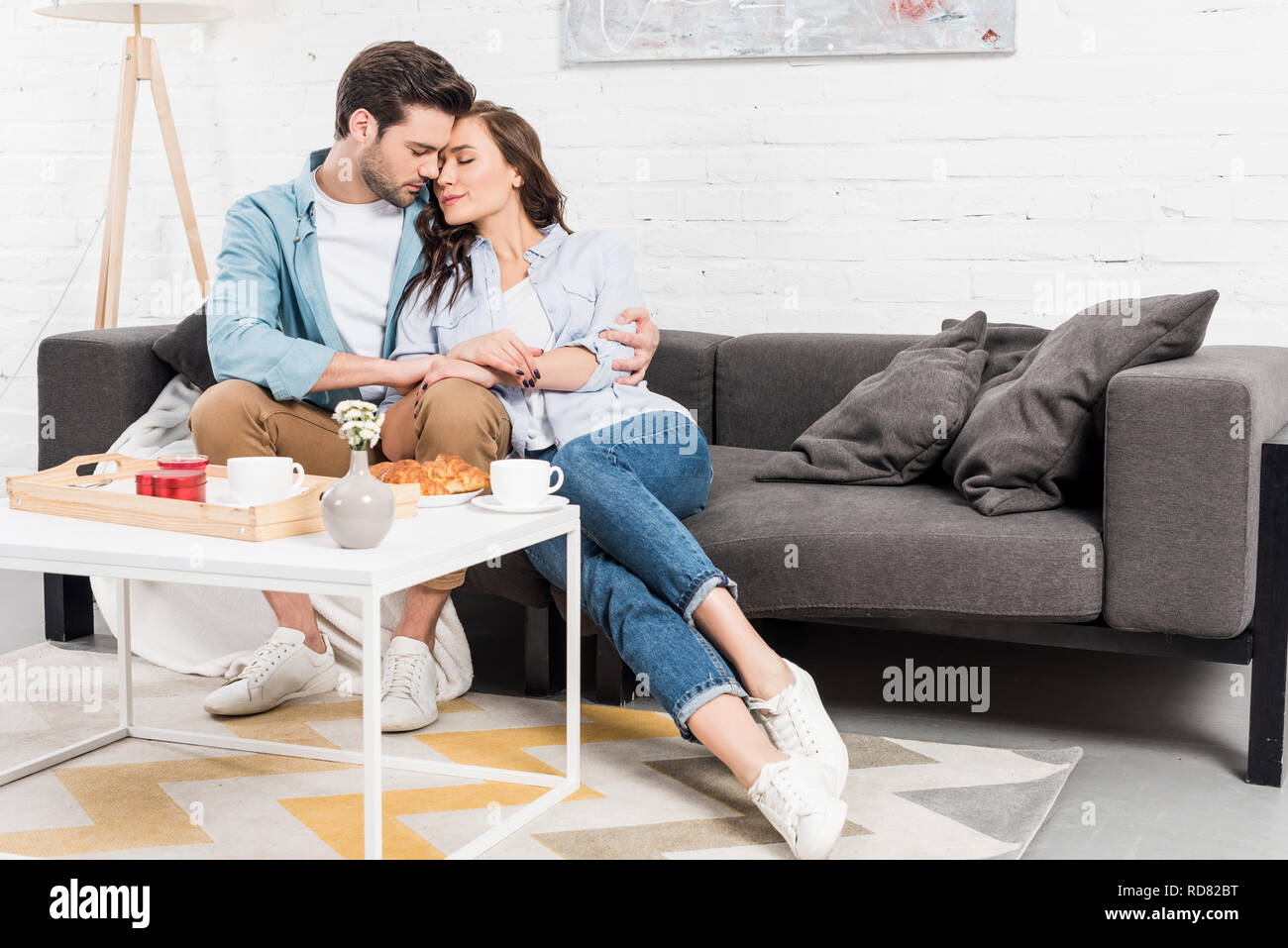 couple sitting on couch and tenderly embracing while having breakfast in living room - Stock Image