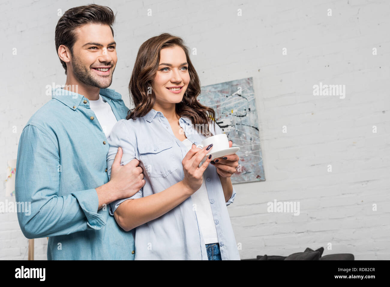 smiling man tenderly embracing beautiful woman holding cup of coffee at home - Stock Image