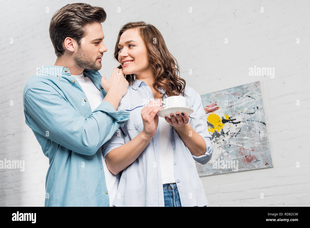 man tenderly embracing attractive woman holding cup of coffee at home - Stock Image