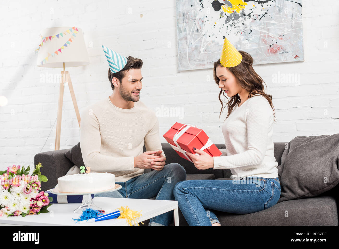 Couple Celebrating Birthday And Man Presenting Gift Box To Woman In Living Room