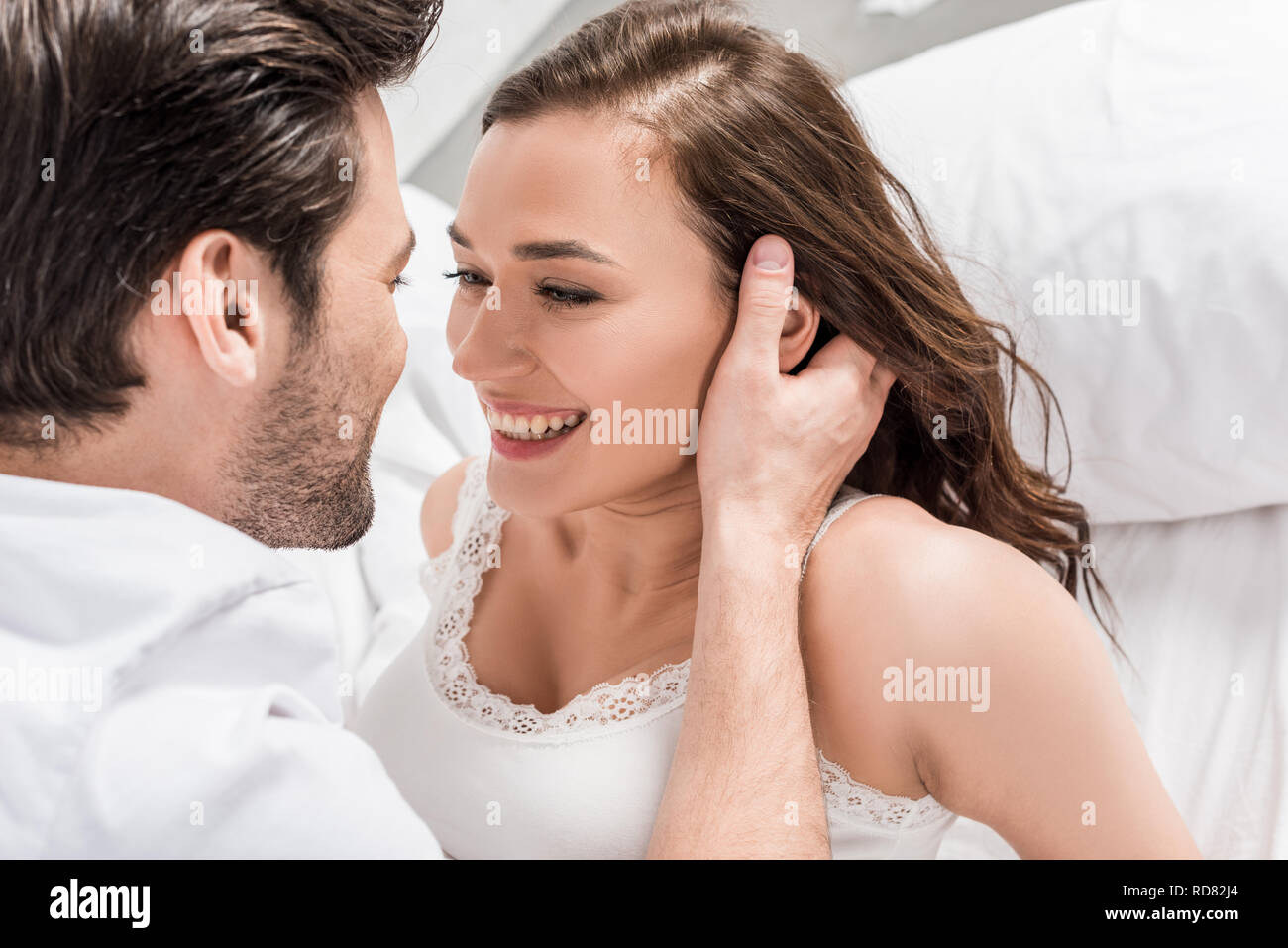 man tenderly touching face of beautiful smiling woman in bed - Stock Image