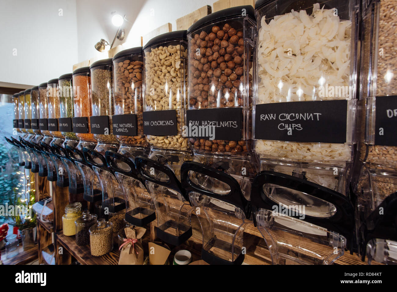 Side view of raw food products displayed in grocery store. Zero waste shopping - shelf with glass jars full of nuts and seeds in organic shop. - Stock Image