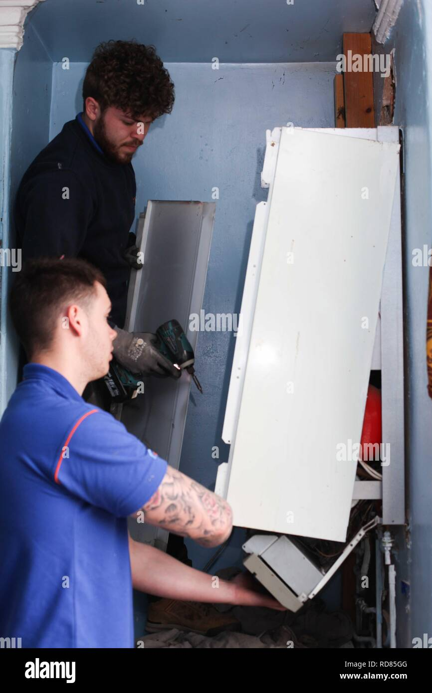 British Gas removing old inefficient boiler ,which creates too much CO2 into the atmosphere .To be replaced by new efficient model .UK government initiative to meet international targets on Climate Change ,such as Paris Accord. At reduced cost . - Stock Image