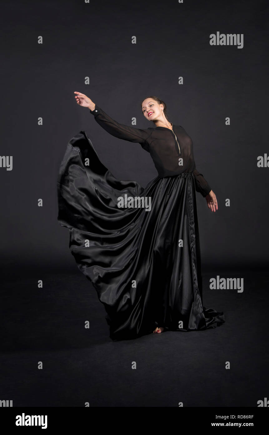 A young,smiling girl in black suit dancing modern choreography.Studio shot on dark background, isolated image. - Stock Image