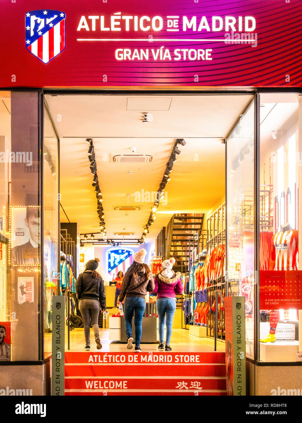 Atletico de Madrid official store on Gran Via shopping street. Three girls entering the official club shop of Atletico football club. - Stock Image