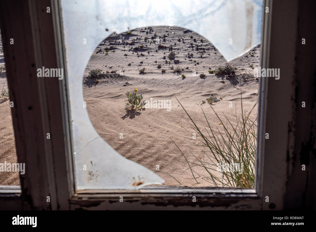 View through broken glass window in Kolmanskop Ghost Town - Luderitz, Namibia, Africa - Stock Image