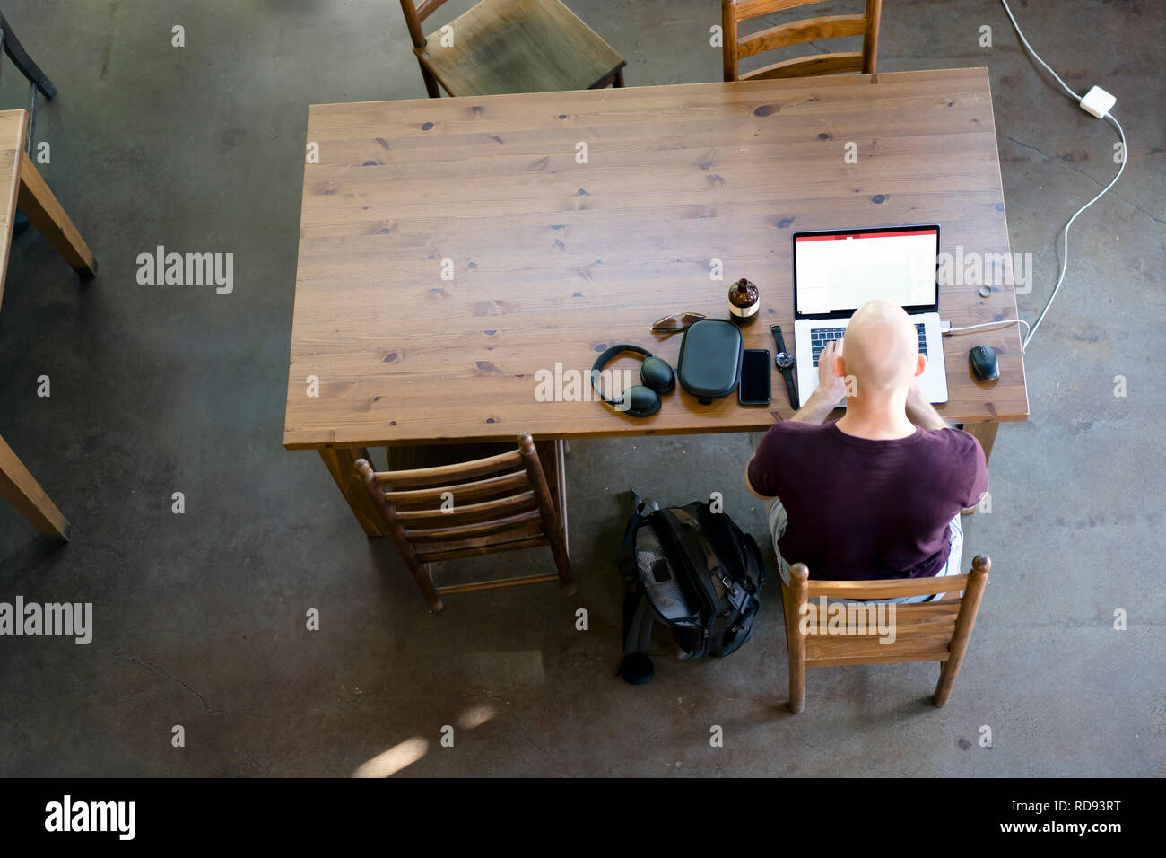 A man in t-shirt working on a laptop is closely watching changes on the laptop display sitting at rectangular wooden table in a local popular coffee s - Stock Image