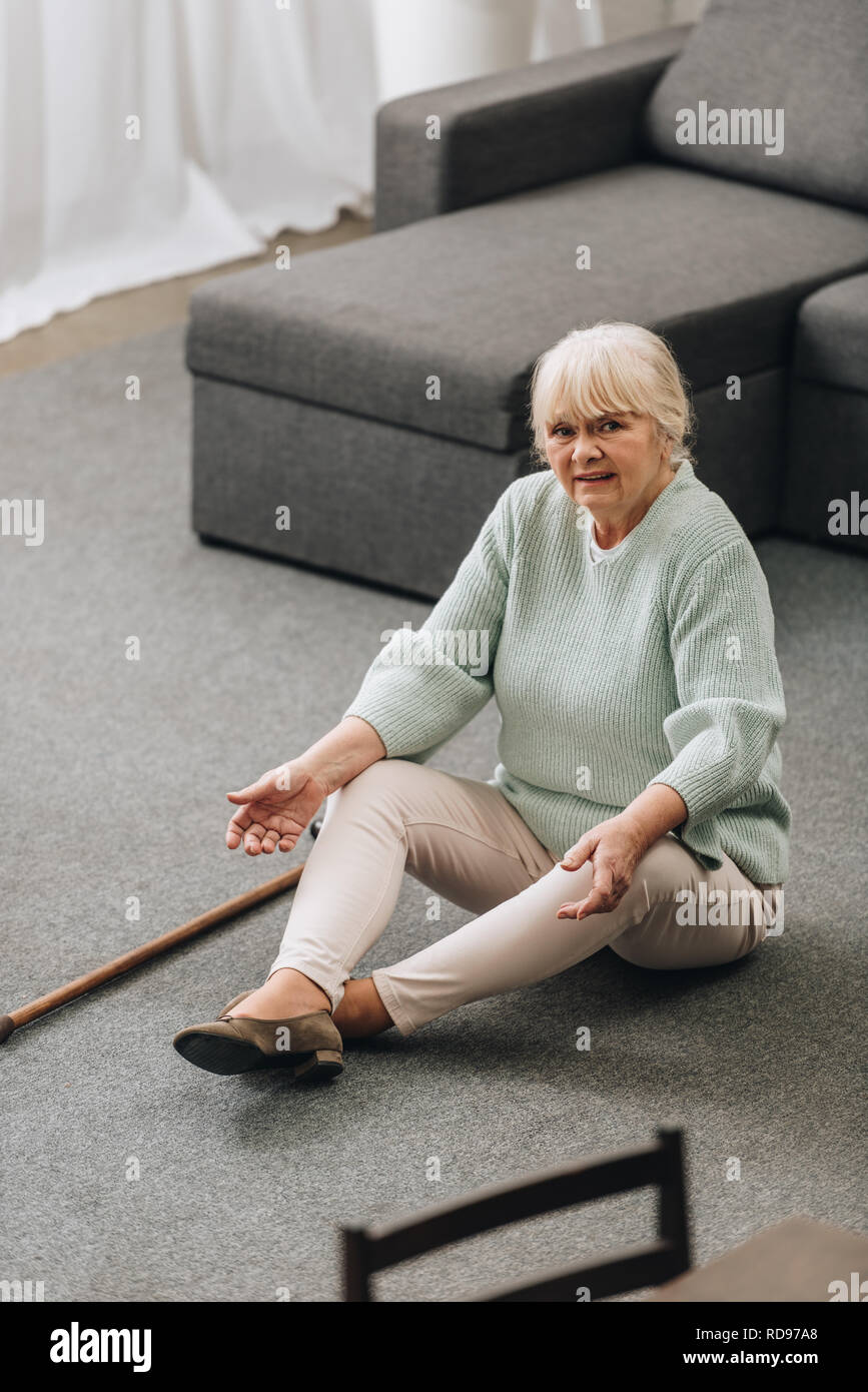 lonely senior woman with blonde hair sitting on floor with walking