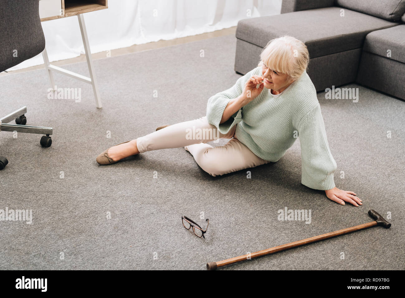 lonely senior woman with blonde hair sitting on floor in living room - Stock Image
