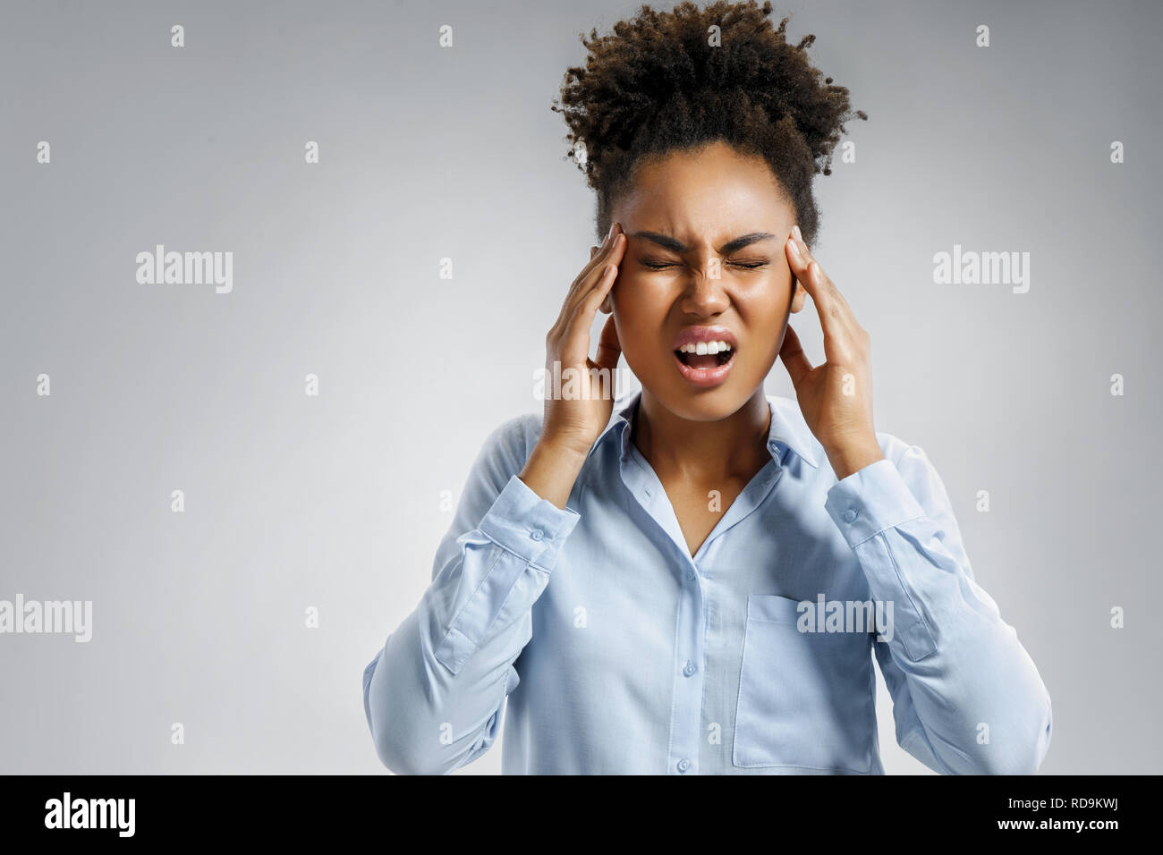 Woman with pain in her temples. Photo of african american woman in blue shirt suffering from stress or a headache grimacing in pain on gray background - Stock Image