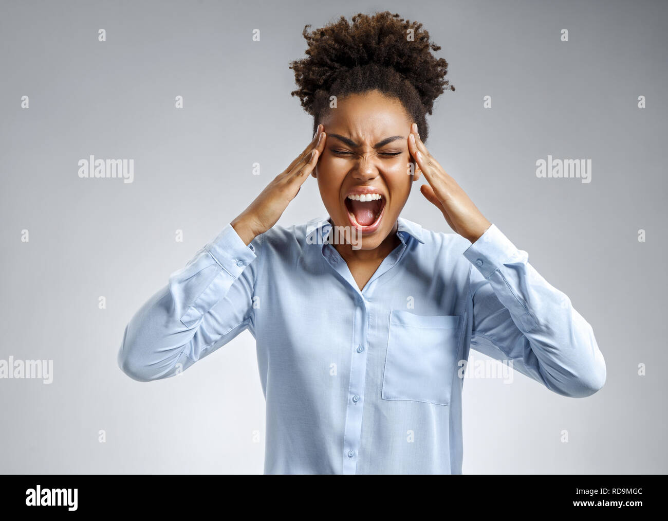 Woman suffering from stress or a headache grimacing in pain. Photo of african american woman in blue shirt on gray background. Medical concept. - Stock Image