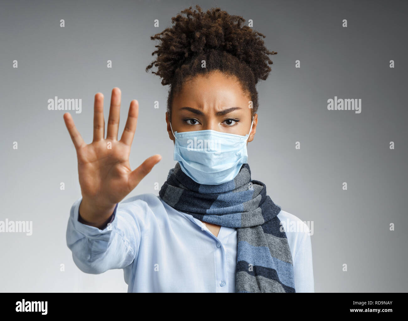 Stop the infection! Healthy woman showing gesture 'stop'. Photo of african american woman wears protective mask against infectious diseases and flu on - Stock Image